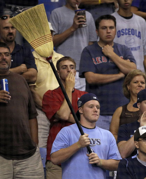 A Tampa Bay Rays fan holds a broom after the Rays defeated the Boston Red Sox 6-4 to sweep a three-game baseball series Wednesday, July 7, 2010, in St. Petersburg, Fla.
