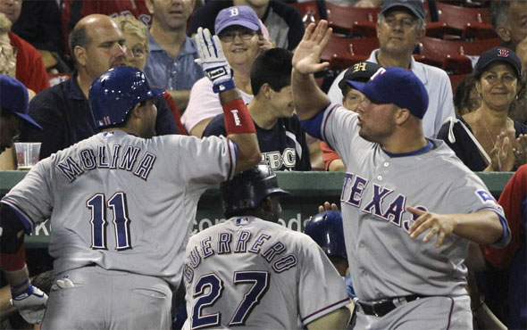 Texas Rangers' Bengie Molina, left, is congratulated by starting pitcher Colby Lewis, right, after Molina's grand slam off Boston Red Sox pitcher Fernando Cabrera during the fifth inning of a baseball game in Boston, Friday, July 16, 2010.