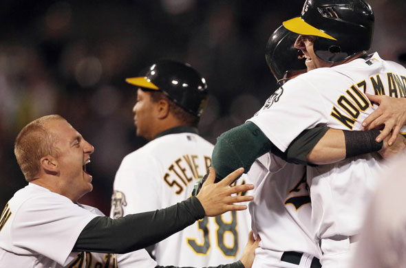 Oakland Athletics' Kevin Kouzmanoff, right, is congratulated by teammates including Cliff Pennington, left, after hitting the game-winning single during the tenth inning of a baseball game against the Boston Red Sox Tuesday, July 20, 2010, in Oakland, Calif.