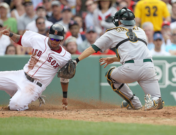 Boston Red Sox player Darnell McDonald is tagged out at home by Oakland's Kurt Suzuki. . Boston Red Sox vs Oakland Athletics