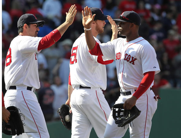 Adrian Gonzalez, Carl Crawford, and Daniel Bard of the Boston Red Sox celebrate defeating the Oakland Athletics, 6-3, at Fenway Park on June 5, 2011 in Boston, Massachusetts