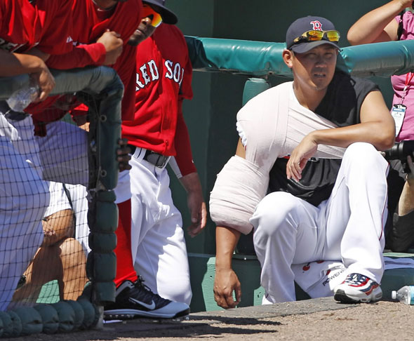 With his pitching arm wrapped in ice, Boston Red Sox pitcher Daisuke Matsuzaka watches Boston's spring training baseball game against the Baltimore Orioles from the dugout in Fort Myers, Fla., Monday, March 7, 2011. Matsuzaka threw in the bullpen earlier in the day.