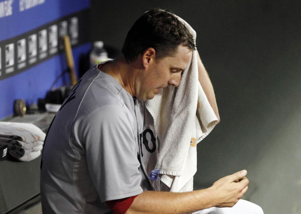 John Lackey sits in the dugout after he was pulled from the game in the fourth inning of the baseball game against the Texas Rangers in Arlington, Texas, Saturday, April 2, 2011.