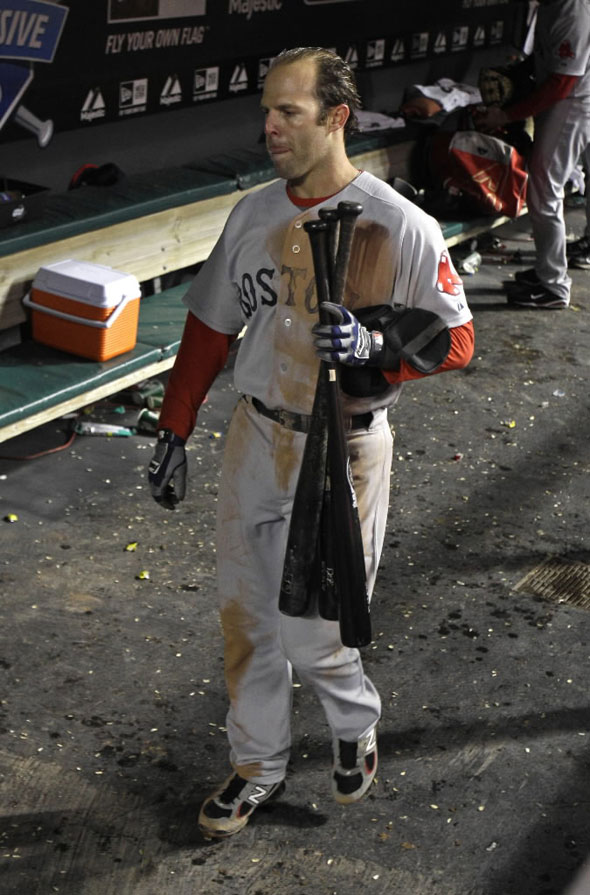 Dustin Pedroia collects bats in the dugout after the Red Sox lost to the Cleveland Indians 3-1 in a baseball game Tuesday, April 5, 2011, in Cleveland.