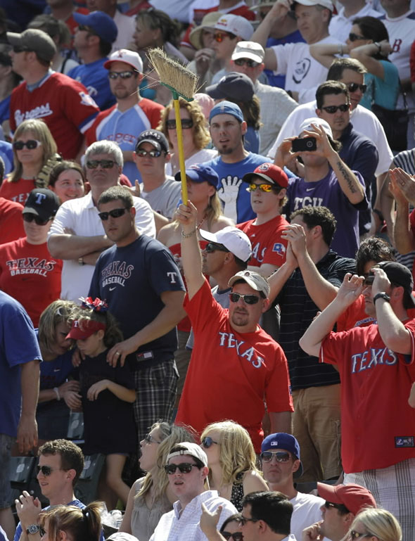 A fan waves a broom as others stand in the closing minutes of an MLB baseball game between the Boston Red Sox and the Texas Rangers on Sunday, April 3, 2011, in Arlington, Texas. The Rangers won 5-1, sweeping the Red Sox in the Rangers' weekend season opener.