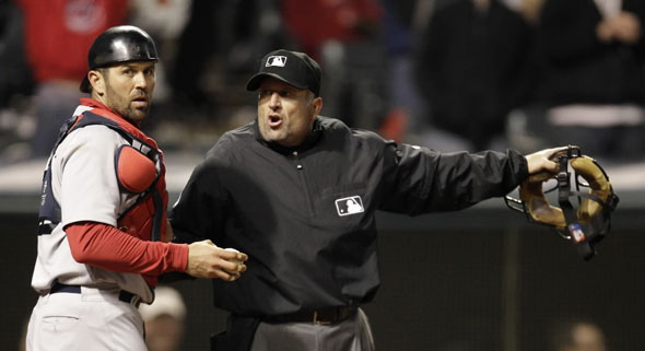 Home plate umpire Dale Scott, right, tells Boston Red Sox catcher Jason Varitek that Cleveland Indians' Travis Buck is safe at home plate in the sixth inning in a baseball game, Wednesday, April 6, 2011, in Cleveland. Buck scored on a fielders choice for Michael Brantley. The Indians won 8-4.