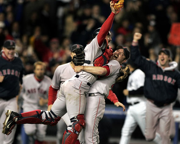 Red Sox catcher Jason Varitek and pitcher Alan Embree embrace as the rest of the Boston players rush out of the Yankee Stadium dugout to begin the celebration following the final out of the Game Seven