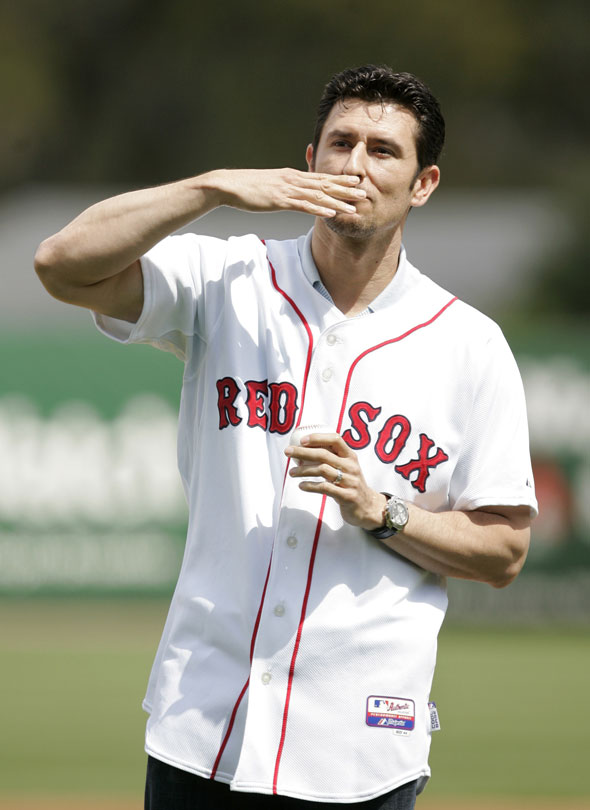 Former Boston Red Sox shortstop Nomar Garciaparra, who signed a Red Sox one-day minor league baseball contract, blows a kiss to the crowd as he takes the field to throw out a ceremonial first pitch at City of Palms Park, in Fort Myers, Fla., Wednesday, March 10, 2010.
