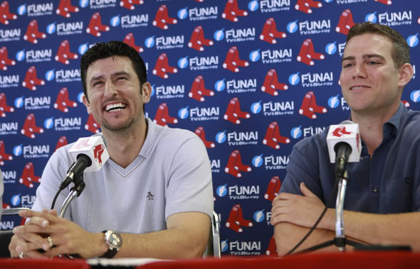 Former Boston Red Sox shortstop Nomar Garciaparra takes questions from reporters as Red Sox general manager Theo Epstein looks on during a news conference at City of Palms Park in Fort Myers, Fla., Wednesday, March 10, 2010.