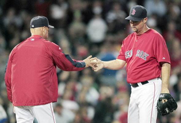 Tim Wakefield, right, hands the ball to manager Terry Francona while leaving the game in the fourth inning of a baseball game against the Kansas City Royals, Friday, May 28, 2010, in Boston.
