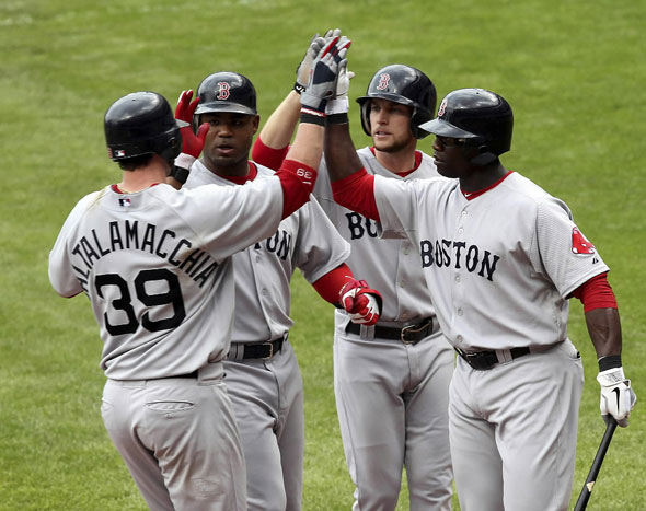 Jarrod Saltalamacchia is congratulated by teammates Carl Crawford, Jed Lowrie and Mike Cameron after hitting a three run home run during the sixth inning of the Red Sox MLB American League baseball game against the Cleveland Indians in Cleveland, Ohio