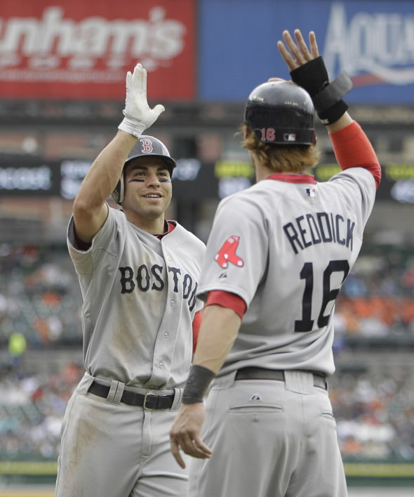 Jacoby Ellsbury is greeted at homeplate by teammate Josh Reddick after his three-run home run in the second inning of a baseball game against the Detroit Tigers in Detroit, Thursday, May 26, 2011.
