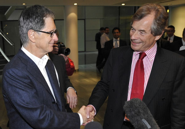John Henry, left, the financier who heads New England Sports Ventures, owners of the Boston Red Sox, and  Liverpool's soccer club chairman Martin Broughton shake hands at a lawyers office in London, Friday, Oct. 15, 2010, where  Liverpool FC's club directors are meeting.