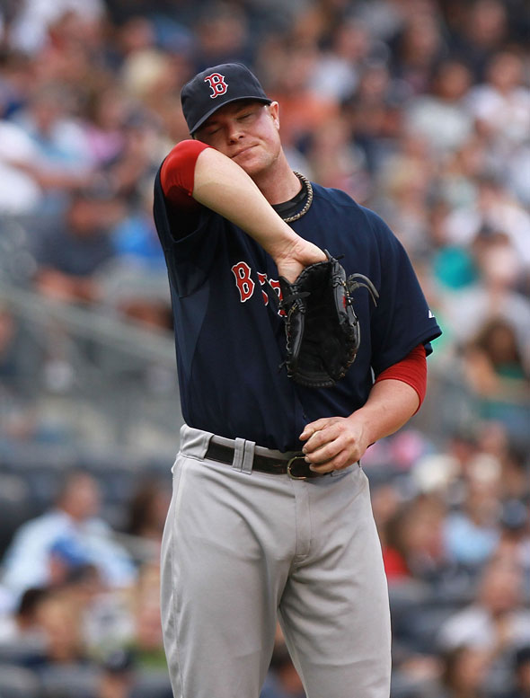 Jon Lester of the Boston Red Sox wipes sweat from his face against the New York Yankees on September 24, 2011 at Yankee Stadium in the Bronx borough of New York City.