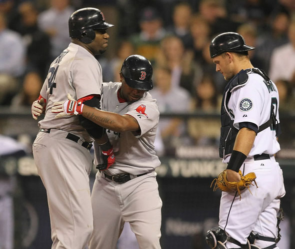 David Ortiz is hugged by Red Sox's Yamaico Navarro at the plate as Seattle Mariners catcher Adam Moore looks on
