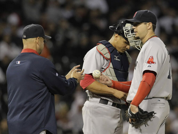 Red Sox manager Terry Francona, left, relieves starting pitcher Josh Beckett, right, as catcher Victor Martinez, looks on during the seventh inning of a baseball game against the Chicago White Sox, Wednesday, Sept. 29, 2010, in Chicago. (
