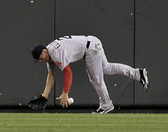 Boston Red Sox center fielder Jacoby Ellsbury falls to the ground after slamming into the fence trying to catch a ball hit by Robert Andino of the Baltimore Orioles in the sixth inning of their MLB American League baseball game in Baltimore, Maryland September 26, 2011. Andino was credited with a three-run inside the park home run.