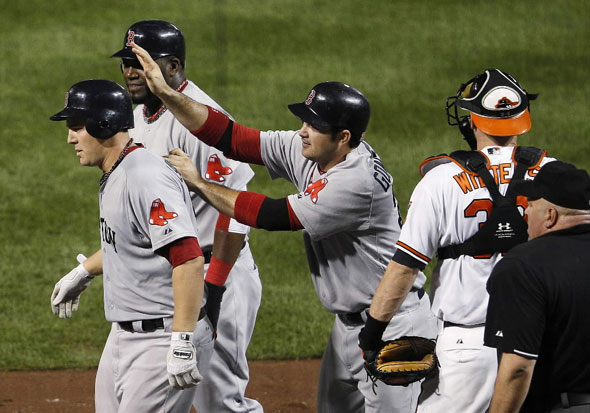 Ryan Lavarnway, left, walks away from home plate with teammates David Ortiz, second from left, and Adrian Gonzalez after Lavarnway drove the two in on a home run in the fourth inning of a baseball game against the Baltimore Orioles on Tuesday, Sept. 27, 2011, in Baltimore. At right is Orioles catcher Matt Wieters.