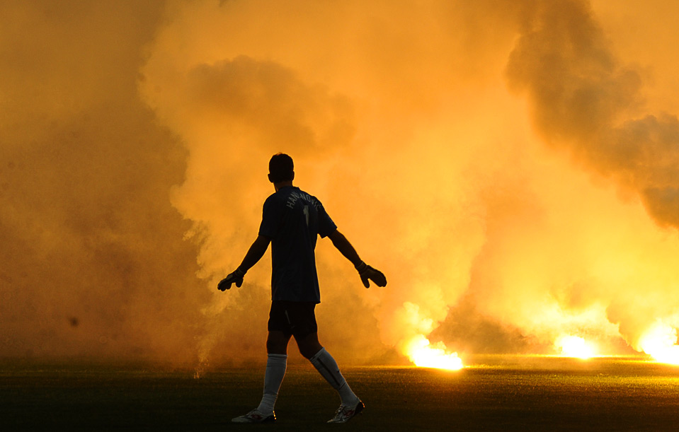 A Polish player is silhouetted by torches thrown by Slovenian supporters onto the pitch during the World Cup 2010 qualifying soccer match between Slovenia and Poland in Maribor, Slovenia September 9. (HRVOJE POLAN/AFP/Getty Images) #