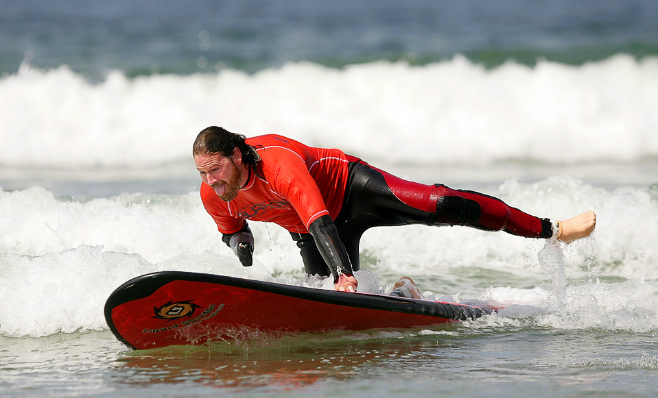 Triple amputee Jake Speed rides a wave during Operation Restoration IV August 15 in Pismo Beach, an event hosted by The Association of Amputee Surfers, an organzation helping wounded soldiers and civilians to learn adaptive surfing. (Ezra Shaw/Getty Images)