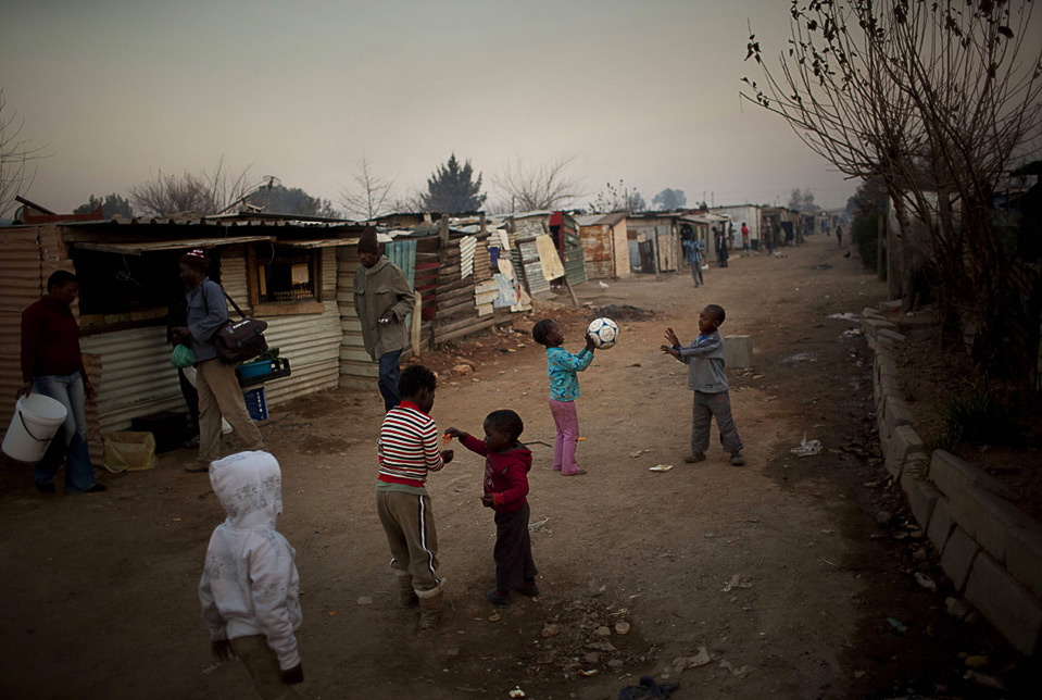 South African children play with a soccer ball in a street in ...