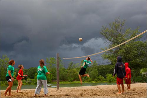 Buy photographs by Joanne Rathe The staff at the Arlington Reservoir plays vollyball on an empty beach, the threatening skies keeping swimmers away.