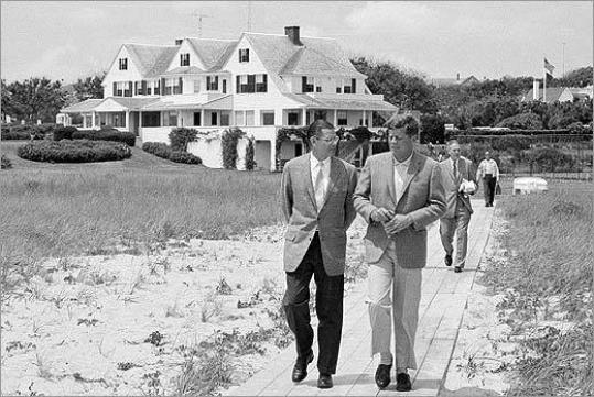 President John F. Kennedy (right) walked with Secretary of Defense Robert McNamara towards a pier to board the Kennedy family cruiser at Hyannis Port.