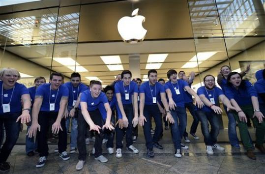 FILE-In this Friday, March 16, 2012, photo, Apple employees welcome hundreds of customers in front of the Apple store at a shopping mall in Oberhausen, western Germany, as the new iPad goes on sale at the Apple store. On Monday, Aug. 20, 2012, Apple set a new record for the most valuable company at $621 billion, beating Microsoft's 1999 high.