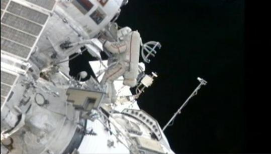 In this still image made from video provided by NASA, a Russian cosmonaut installs shields to protect against zooming pieces of junk to improve the safety of his orbiting home Monday, Aug. 20, 2012. Gennady Padalka and Yuri Malenchenko hung the panels on the Russian side of the International Space Station, after moving a bulky crane and tossing overboard a small spherical satellite on Monday.
