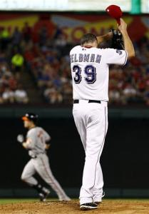 Texas Rangers starting pitcher Scott Feldman (39) reacts after giving up a two-run home run to Baltimore Orioles' Nate McLouth, rear, in the fifth inning of a baseball game, Tuesday, Aug. 21, 2012, in Arlington, Texas.