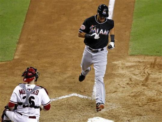 Miami Marlins' Gorkys Hernandez scores on an RBI single by Giancarlo Stanton as Arizona Diamondbacks catcher Miguel Montero watches during the 10th inning of a baseball game, Tuesday, Aug. 21, 2012, in Phoenix.