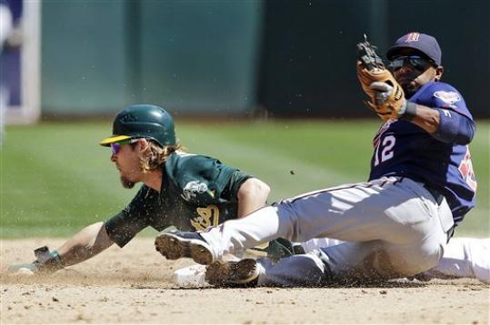 Minnesota Twins second baseman Alexi Casilla, right, tags out Oakland Athletics' Josh Reddick on a steal attempt during the fifth inning of a baseball game, Wednesday, Aug. 22, 2012, in Oakland, Calif.