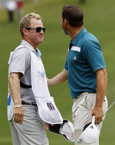 Caddie David Faircloth, left, smiles at Sergio Garcia, of Spain, on the 18th green following Garcia's victory in the rain-delayed Wyndham Championship golf tournament in Greensboro, N.C., Monday, Aug. 20, 2012.