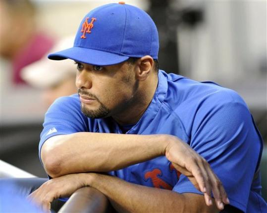 FILE - In this file photo taken Aug. 10, 2012, New York Mets pitcher Johan Santana watches from the dugout a baseball game in New York. Santana is headed to the disabled list and not expected to pitch again this season. General manager Sandy Alderson said Wednesday, Aug. 22, 2012, that the left-hander was going on the 15-day DL with inflammation in his lower back.