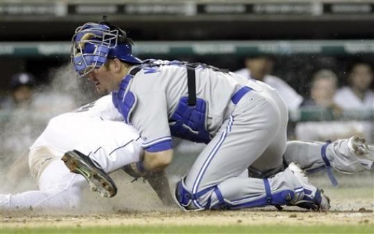 Detroit Tigers' Austin Jackson, left, scores on a single by Prince Fielder as Toronto Blue Jays catcher Jeff Mathis, right, loses the ball in the sixth inning of a baseball game on Wednesday, Aug. 22, 2012, in Detroit.