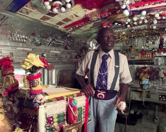 In this 1998 photo, Rev. H.D. Dennis, poses inside 'The House of Prayer,' an ornately decorated school bus at his home at Margaret's Grocery near Vicksburg, Miss. The Rev. Herman 'Preacher' Dennis, who turned a Mississippi Delta grocery store into a folk-art castle that became a roadside attraction, has died, Tuesday, Sept. 4, 2012. He was 96.
