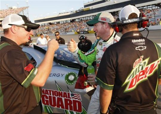 Dale Earnhardt Jr., center, celebrates after qualifying for the NASCAR Sprint Cup Series auto race at Richmond International Raceway in Richmond, Va., Friday, Sept. 7, 2012. Earnhardt Jr. won the pole for Saturday night's race when he turned a lap at 127.023 mph.