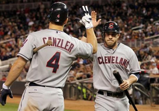 Cleveland Indians' Jason Kipnis, right, is congratulated by teammate Russ Canzler (4) after scoring the go-ahead run on Michael Brantley's RBI-single against Minnesota Twins relief pitcher Alex Burnett during the seventh inning of a baseball game on Friday, Sept. 7, 2012, in Minneapolis.