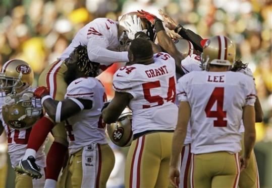 San Francisco 49ers kicker David Akers is congratulated by teammates after kicking a 63-yard field goal during the first half of an NFL football game against the Green Bay Packers Sunday, Sept. 9, 2012, in Green Bay, Wis. Akers tied an NFL record with the 63-yard field goal.