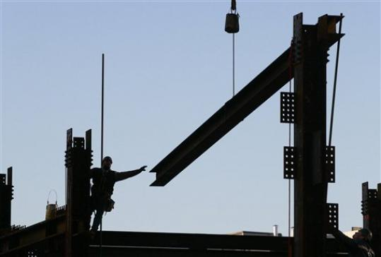 FILE - In this file photo of Jan. 27, 2010, an ironworker reaches for a beam suspended from a crane at One World Trade Center, in New York. Eleven years after terrorists attacked the World Trade Center, the new World Trade Center now dominates the lower Manhattan skyline.