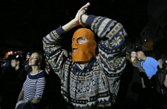 A masked spectator reacts during the concert organized to support jailed Pussy Riot musicians in St.Petersburg, Russia, Sunday, Sept. 9, 2012. A Moscow judge has sentenced each of three members of the provocative punk band Pussy Riot to two years in prison on hooliganism charges following a trial that has drawn international outrage as an emblem of Russia's intolerance to dissent.