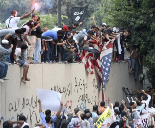 Protesters destroy an American flag pulled down from the U.S. embassy in Cairo, Egypt, Tuesday, Sept. 11, 2012. Egyptian protesters, largely ultra conservative Islamists, have climbed the walls of the U.S. embassy in Cairo, went into the courtyard and brought down the flag, replacing it with a black flag with Islamic inscription, in protest of a film deemed offensive of Islam.