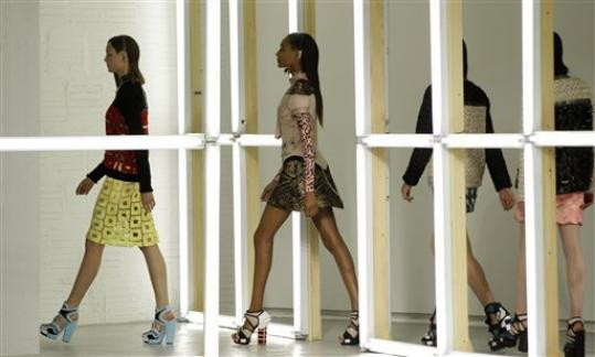 Models walk through a grid of fluorescent lights at the conclusion of the presentation of the Rodarte Spring 2013 collection in New York, Tuesday, Sept. 11, 2012.