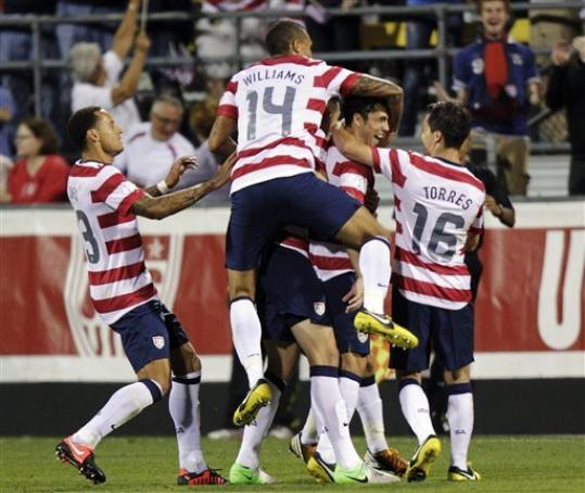 United States players celebrate a goal by Herculez Gomez against Jamaica during the second half of a World Cup qualifying soccer match, Tuesday, Sept. 11, 2012, in Columbus, Ohio. The United States won 1-0.