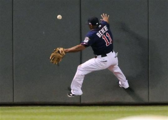 Minnesota Twins center fielder Ben Revere goes up the wall to chase a triple off the bat of Kansas City Royals' Alex Gordon in the third inning of a baseball game, Tuesday, Sept. 11, 2012, in Minneapolis.