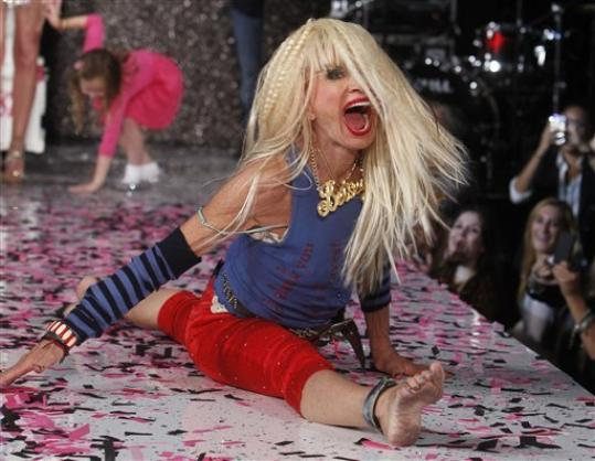 Designer Betsey Johnson goes into a split after doing a cartwheel on the runway after the Betsey Johnson Spring 2013 collection show during Fashion Week, Tuesday, Sept. 11, 2012, in New York.