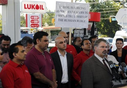 Sal Risalvato, second right, answers a question at a Lukoil service station Wednesday, Sept. 12, 2012, in South Plainfield, N.J., as a large gathering of Lukoil dealers and workers protested what they say are unfair pricing practices by Lukoil North America. More than 50 Lukoil gas stations in New Jersey and Pennsylvania were jacking up prices to more than $8 a gallon Wednesday to protest what they say are unfair pricing practices by Lukoil North America that they say leave them at a competitive disadvantage. Risalvato of the New Jersey Gasoline, Convenience, Automotive Association said the protest was aimed at raising consumer awareness about the challenges facing Lukoil dealers and to get Lukoil to respond to dealer grievances.