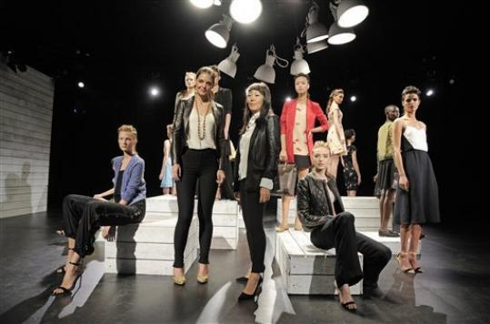 In this photo provided by Holmes & Yang, Katie Holmes, center left, and Jeanne Yang, center right, pose for a portrait in front of the Holmes & Yang Spring 2013 collection during Fashion Week in New York, Tuesday, Sept. 11, 2012.