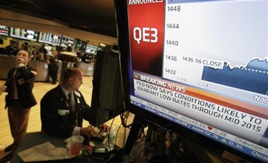 Specialist Frank Babino, center, works at his post on the floor of the New York Stock Exchange Thursday, Sept. 13, 2012. The Federal Reserve unleashed a series of aggressive actions Thursday intended to stimulate the still-weak economy by making it cheaper for consumers and businesses to borrow and spend.