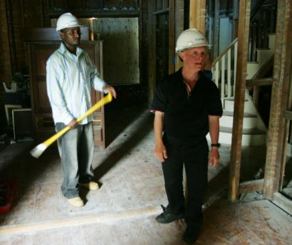 Triangle Inc. worker Peter Muthua (left) joins Gerard Torre, a group home resident he helped after November's explosion, checking on its reconstruction Monday.